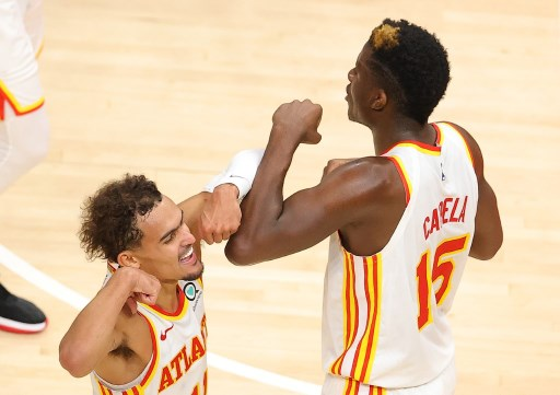 Clint Capela #15 of the Atlanta Hawks reacts after drawing a foul on a basket against the Detroit Pistons with Trae Young #11. Kevin C. Cox/Getty Images/AFP