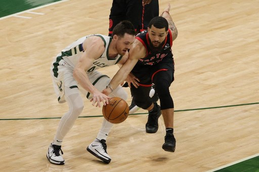 Fred VanVleet #23 of the Toronto Raptors and Pat Connaughton #24 of the Milwaukee Bucks on February 16, 2021 in Milwaukee, Wisconsin.    Stacy Revere/Getty Images/AFP