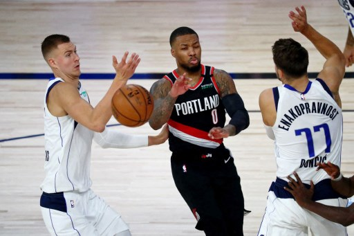 Damian Lillard #0 of the Portland Trail Blazers has the ball knocked loose on a drive against Kristaps Porzingis #6 and Luka Doncic #77 of the Dallas Mavericks. Kim Klement - Pool/Getty Images/AFP