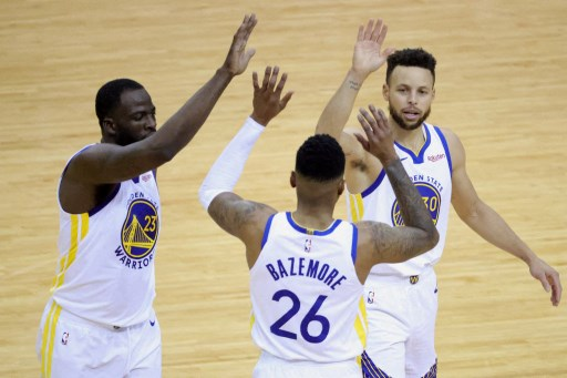 Stephen Curry #30 of the Golden State Warriors high fives Draymond Green #23 and Jordan Poole #3. Carmen Mandato/Getty Images/AFP