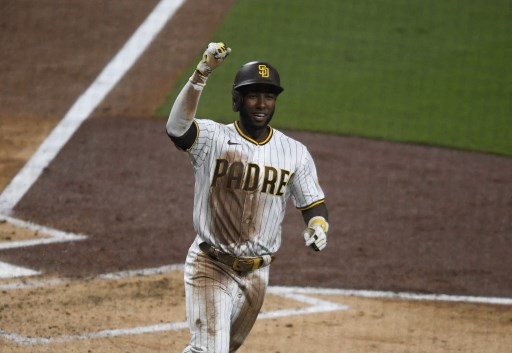Jurickson Profar #10 of the San Diego Padres pumps his fist as he scores during the second inning.  Denis Poroy/Getty Images/AFP