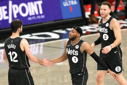 Joe Harris #12 high-fives Bruce Brown #1 and Blake Griffin #2 of the Brooklyn Nets on April 16, 2021 in New York City.  Sarah Stier/Getty Images/AFP