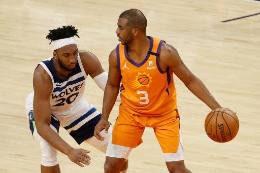 Chris Paul #3 of the Phoenix Suns handles the ball against Josh Okogie #20 of the Minnesota Timberwolves. Christian Petersen/Getty Images/AFP