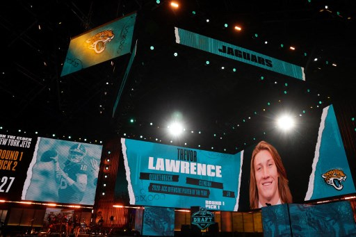 Screens show the Jacksonville Jaguars selection of Trevor Lawrence with the first pick of the 2021 NFL Draft. Gregory Shamus/Getty Images/AFP