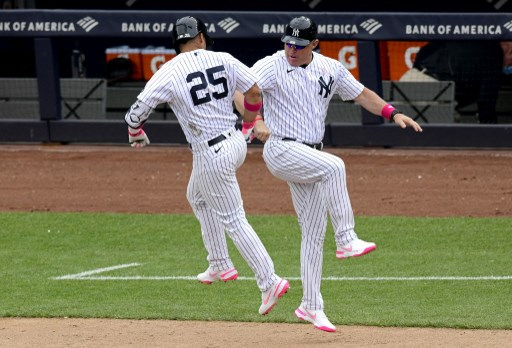 Gleyber Torres #25 of the New York Yankees is congratulated by third base coach Phil Nevin #88