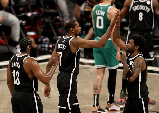 Kyrie Irving #11 of the Brooklyn Nets is congratulated by teammates Kevin Durant #7 and James Harden #13. Elsa/Getty Images/AFP