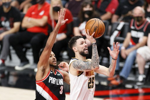 Austin Rivers #25 of the Denver Nuggets shoots against CJ McCollum #3 of the Portland Trail Blazers. Steph Chambers/Getty Images/AFP