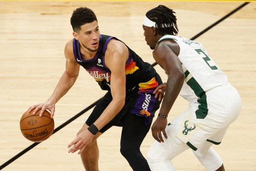 Devin Booker #1 of the Phoenix Suns handles the ball against Jrue Holiday #21 of the Milwaukee Bucks in the second half of game five of the NBA Finals.