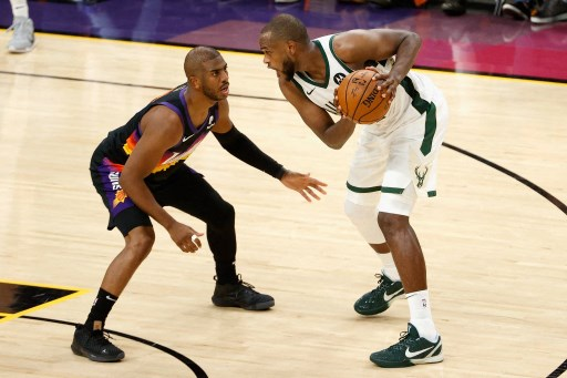 Khris Middleton #22 of the Milwaukee Bucks controls the ball against Chris Paul #3 of the Phoenix Suns . Christian Petersen/Getty Images/AFP