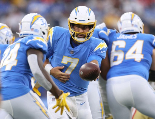 Chase Daniel #7 of the Los Angeles Chargers hands off to Darius Bradwell #34. Harry How/Getty Images/AFP